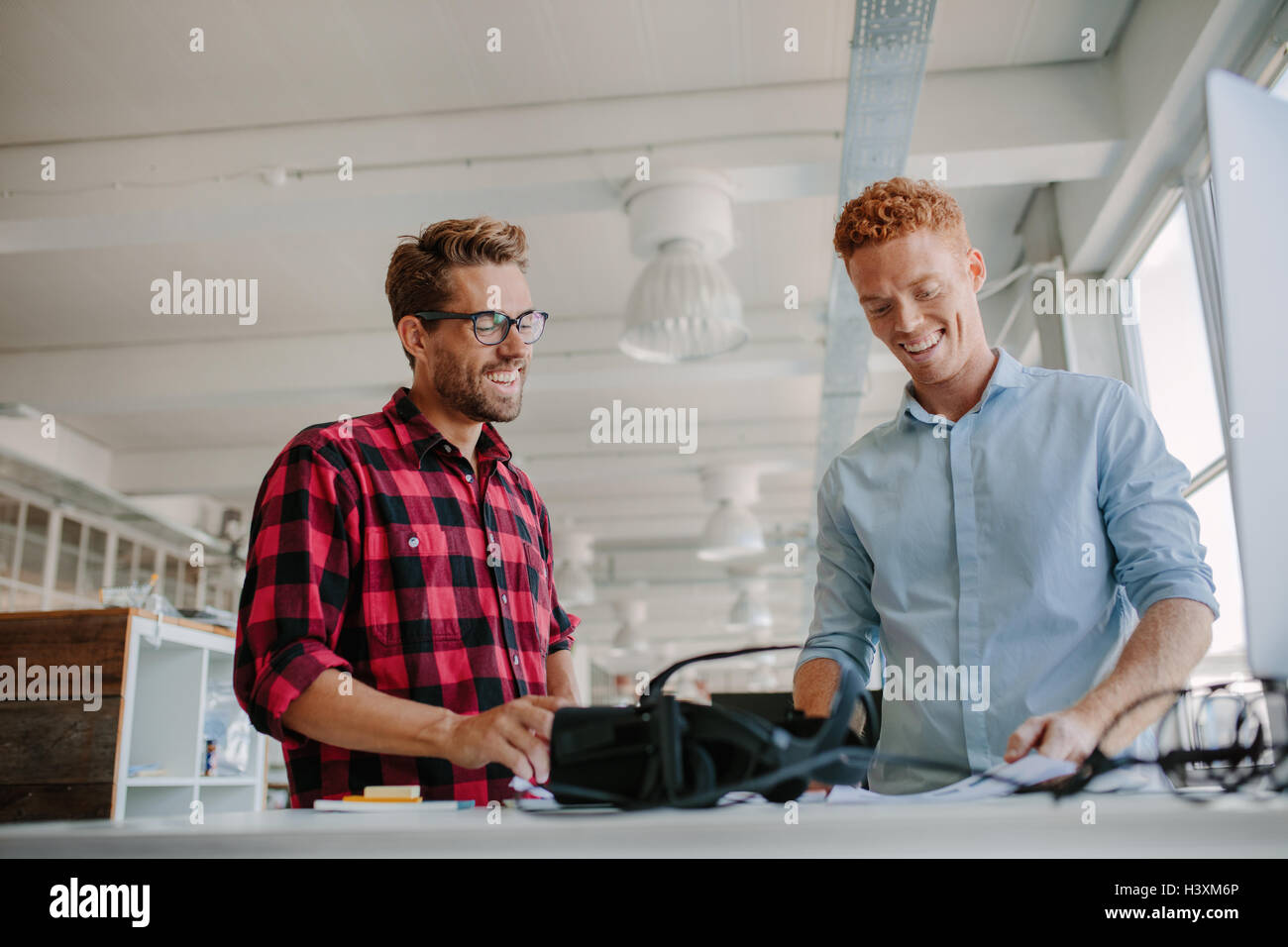 Shot of happy young man working together in modern office. Team of developers working on testing new virtual reality - Stock Image