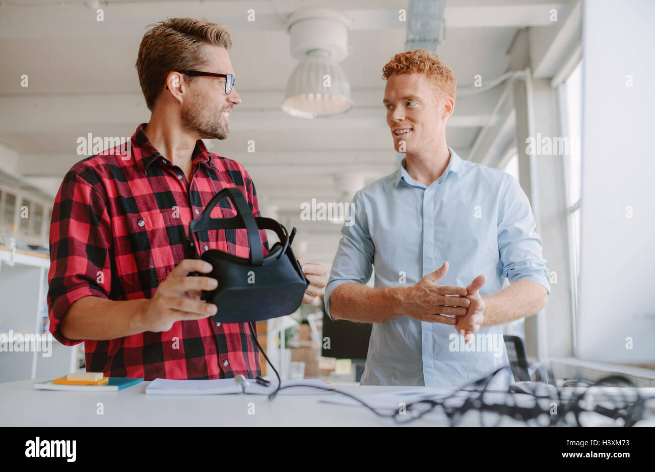 Shot of two young developers discussing on new virtual reality glasses. Business colleagues working on developing - Stock Image