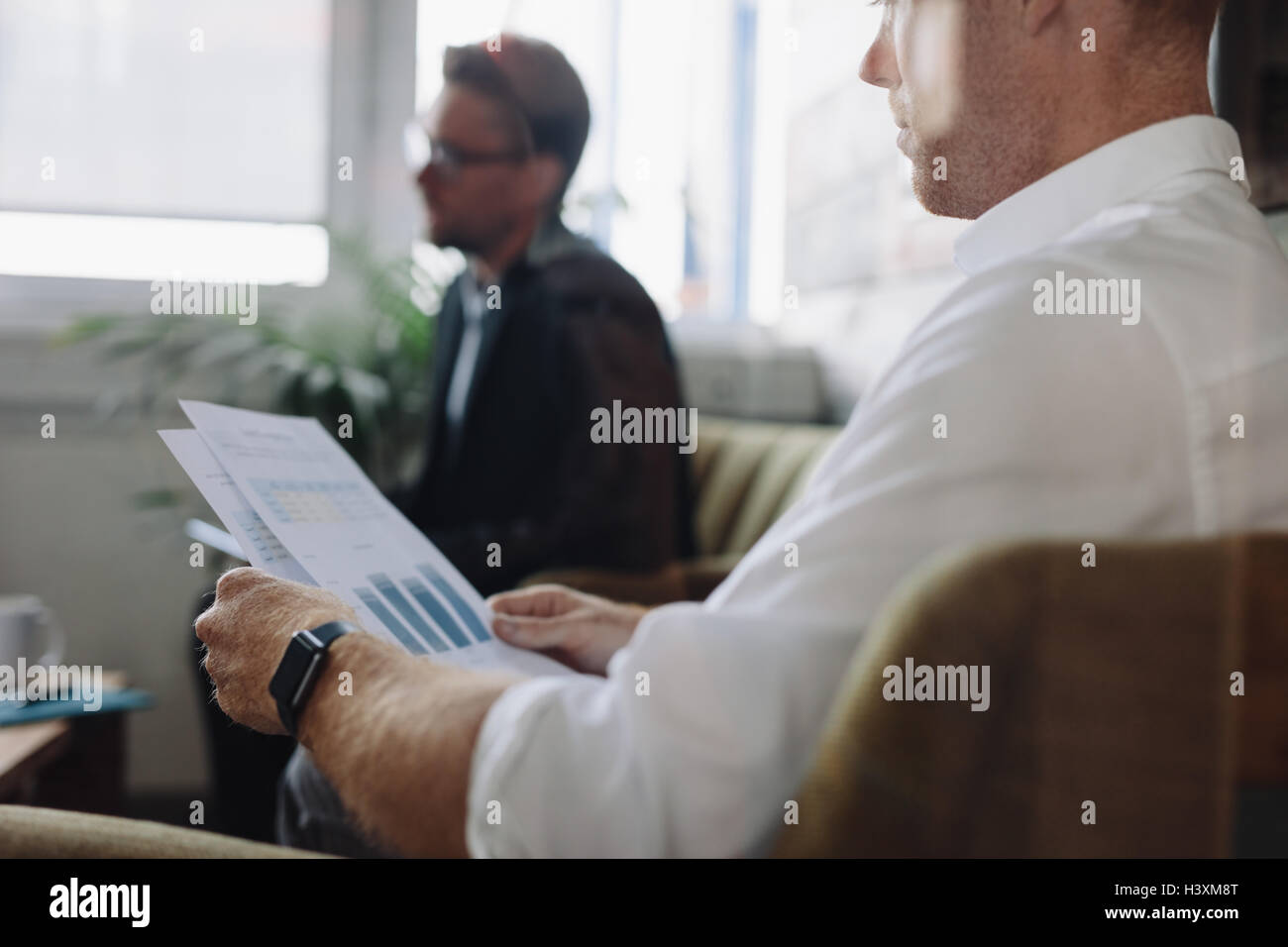 Shot of business people sitting in office and going through business reports. Businessman reading charts during - Stock Image