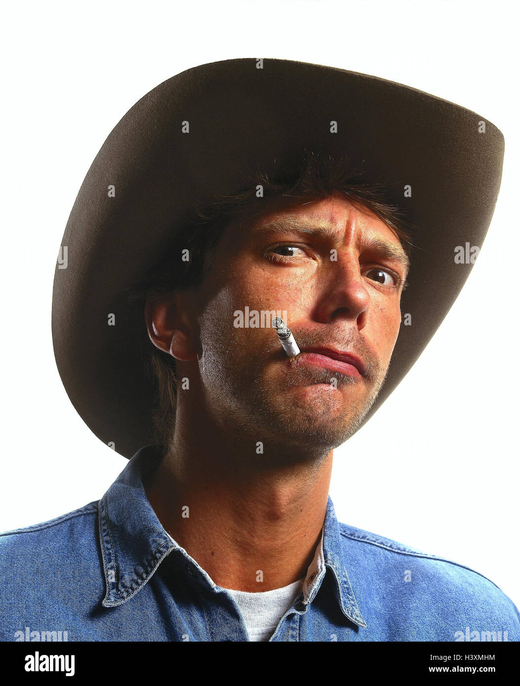 Man, stetson, cigarette, portrait, inside, young, care, facial play, seriously, fiercely, smoke, nicotine, warn, warning, threat, threaten, nastily, malice, resolutely, determination, crustily, irritable, grows bitter, studio, cut out Stock Photo