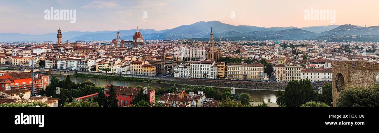 panorama of Florence city downtown at sunrise against distant hills from elevated lookout over Arno river to historic - Stock Image