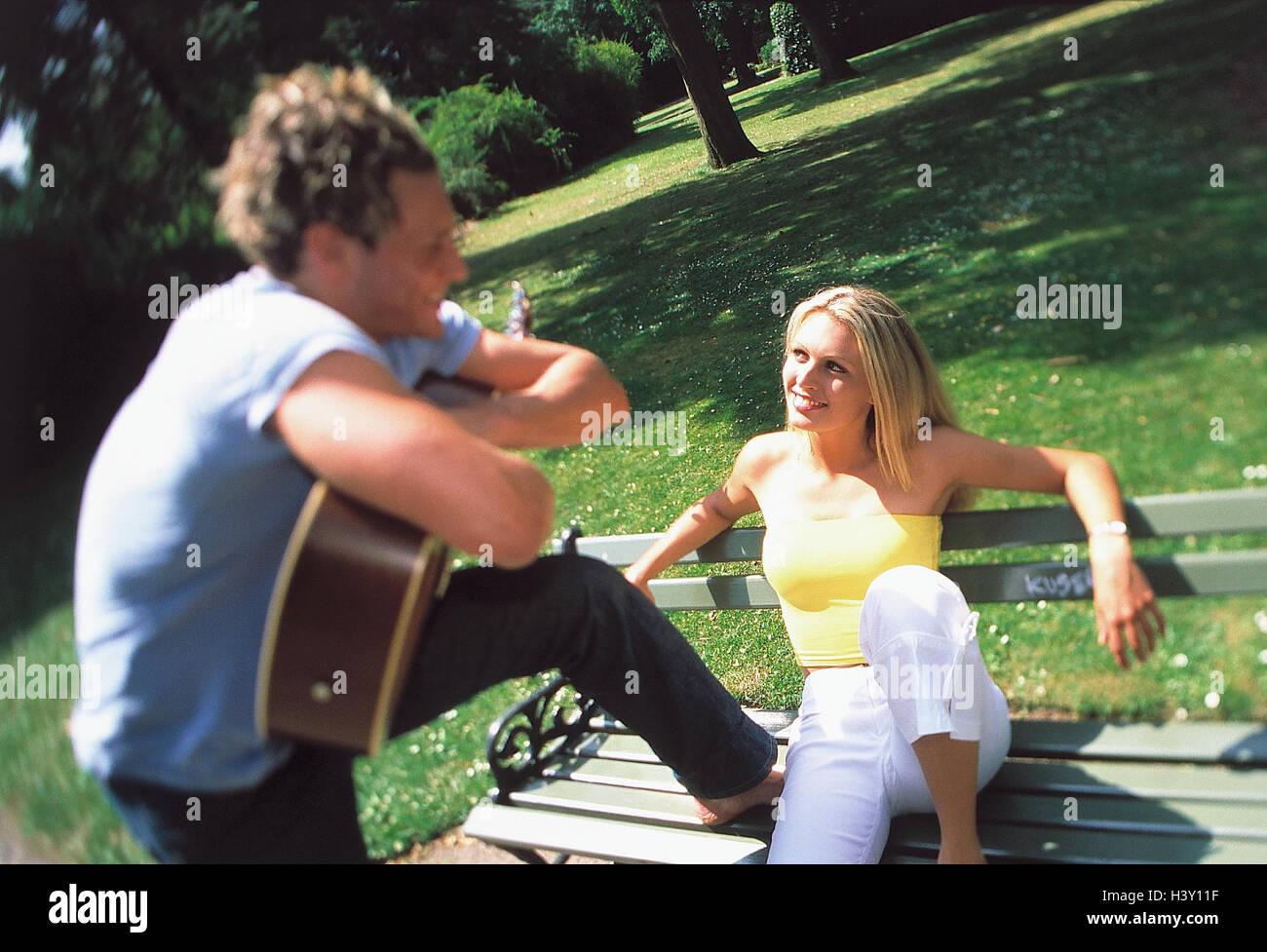 Park, woman, bank, sit, man, guitar, eye contact, outside, park-bench, summer, flirtation, flirt, couple, excursion, - Stock Image