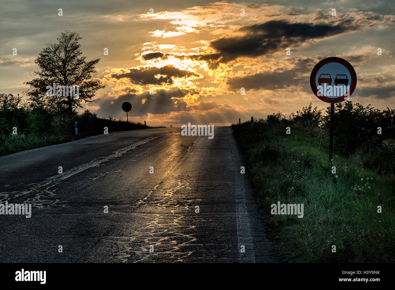 No overtaking sign by an old and damaged road in a dramatic sunset - Stock Image