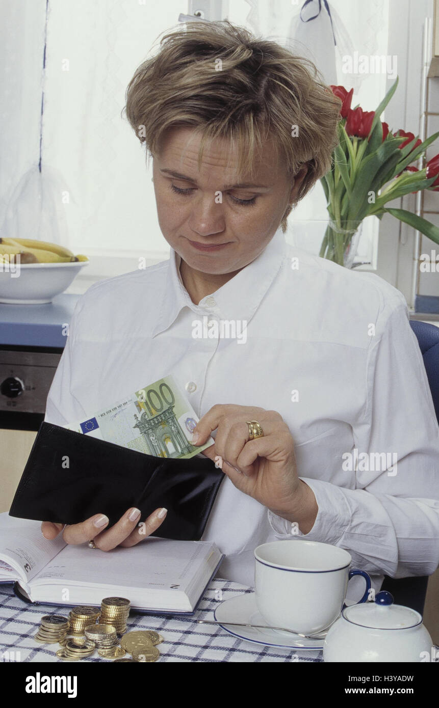 Woman, young, housekeeping money, change purse, banknotes, notebook, dealts with, model released, budget, outputs, - Stock Image