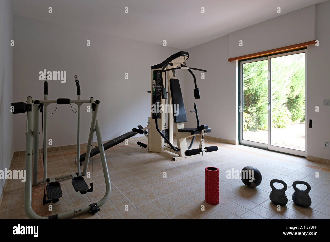 Exercise machines and kettlebells on a home gym - Stock Image