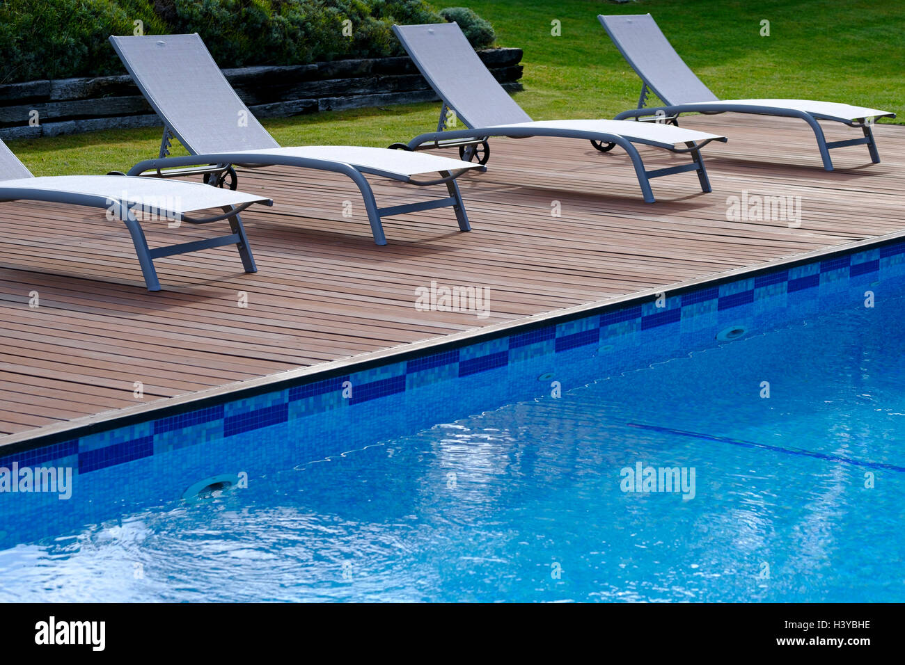 Lounge chairs on wooden deck next to an outdoor swimming ...