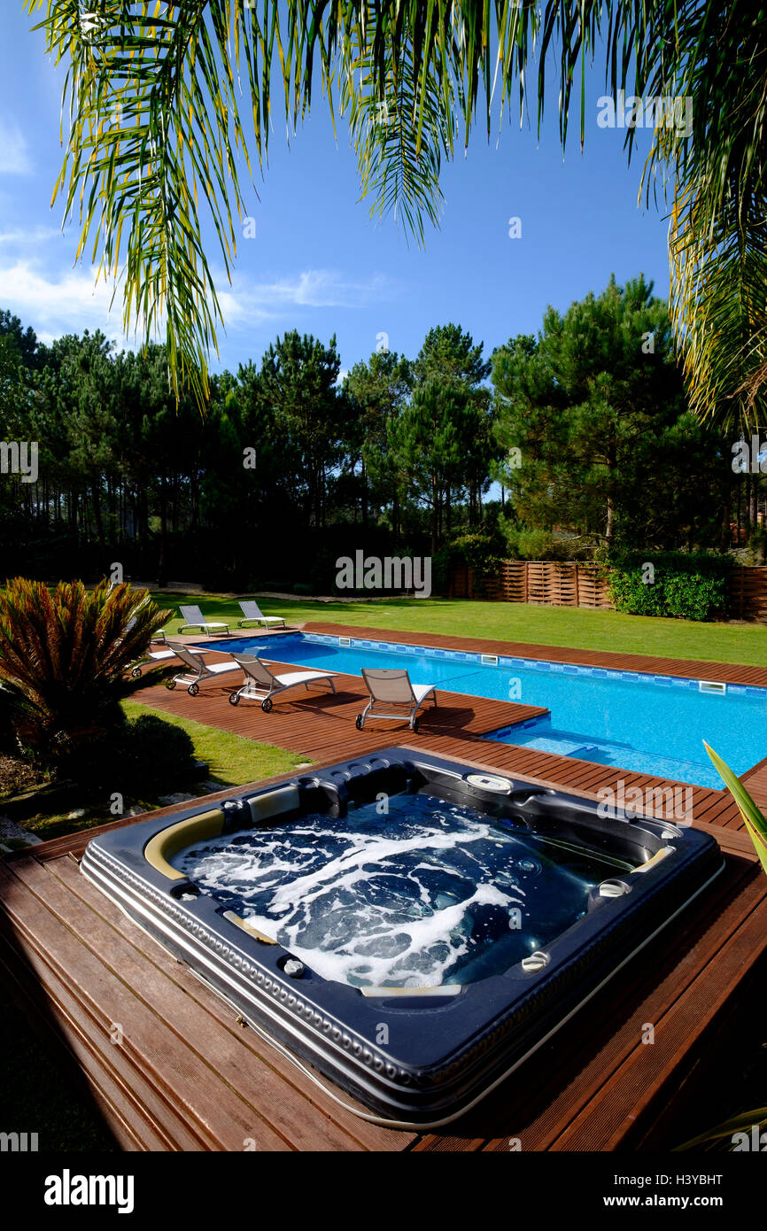 Jacuzzi next to an outdoor swimming pool - Stock Image