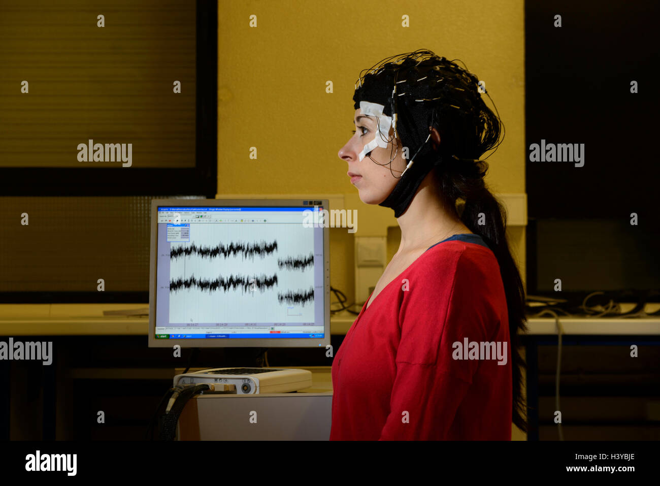 Person undergoing an electroencephalogram with an EEG cap to scan her brain's electrical activity - Stock Image