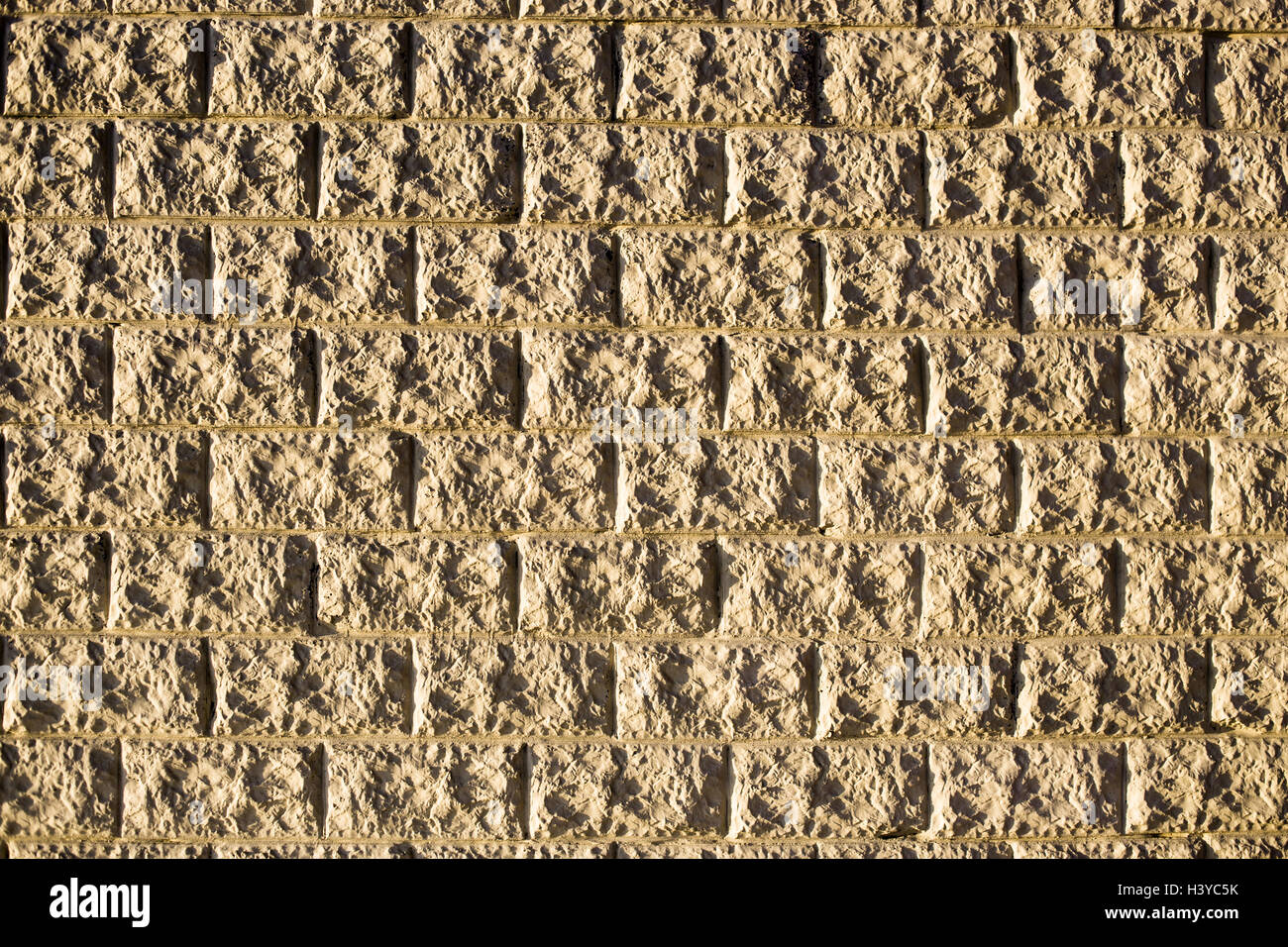 Wall of structured decorative light bricks as background or texture in natural sunlight Stock Photo