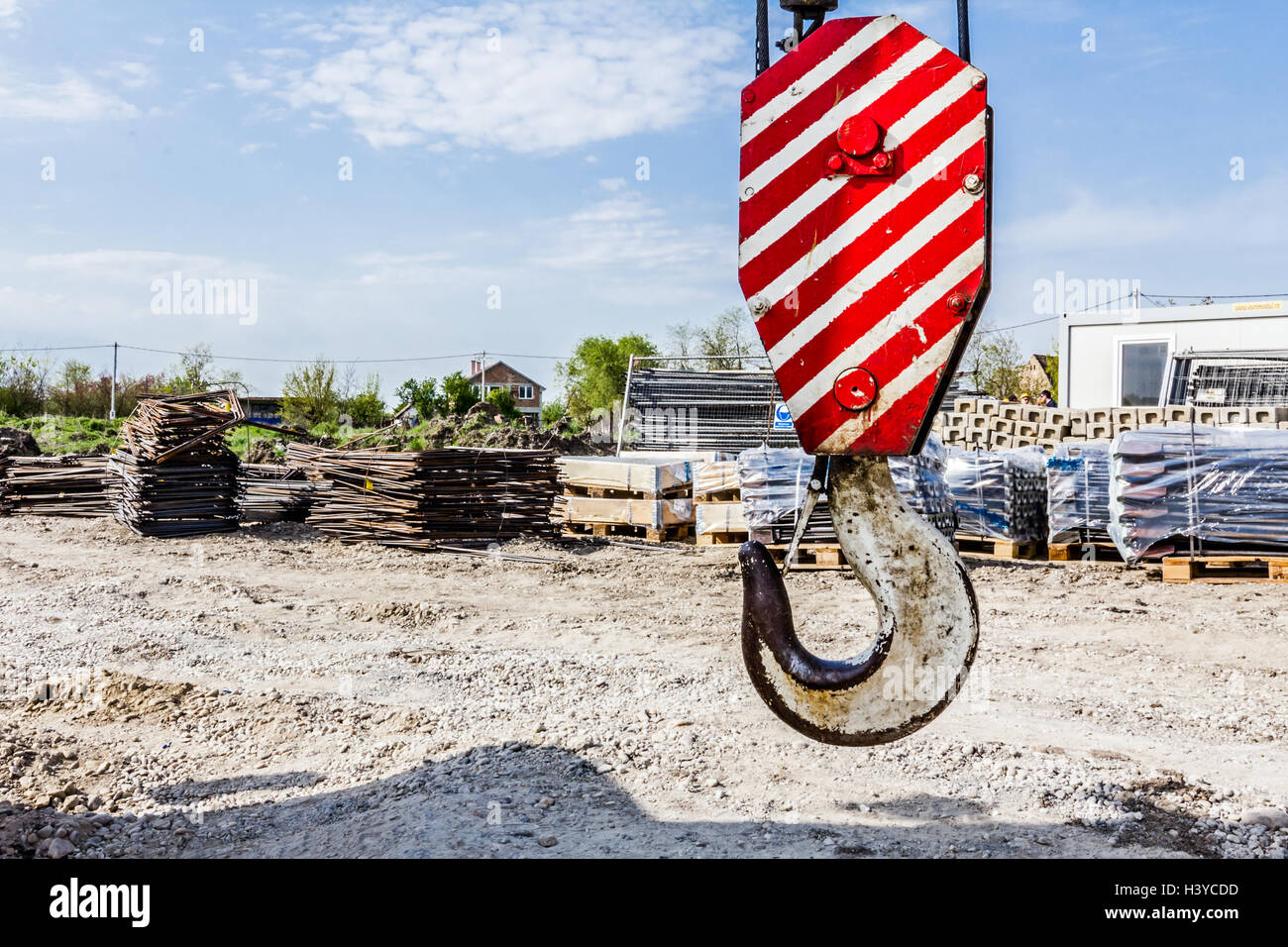 White crane hook with red stripes is hanging, armature stack in background. - Stock Image
