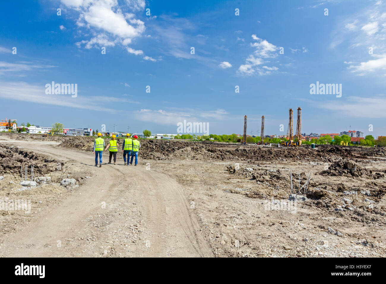 Engineers in hardhats inspecting a work site discussing about work plan. - Stock Image