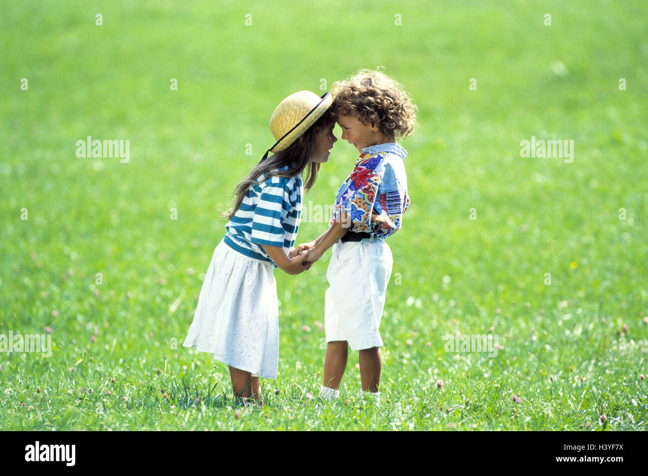 Meadow, girl, boy, hands hold, eye contact, outside, children, two, comradeship, affection, friends, friendship, - Stock Image