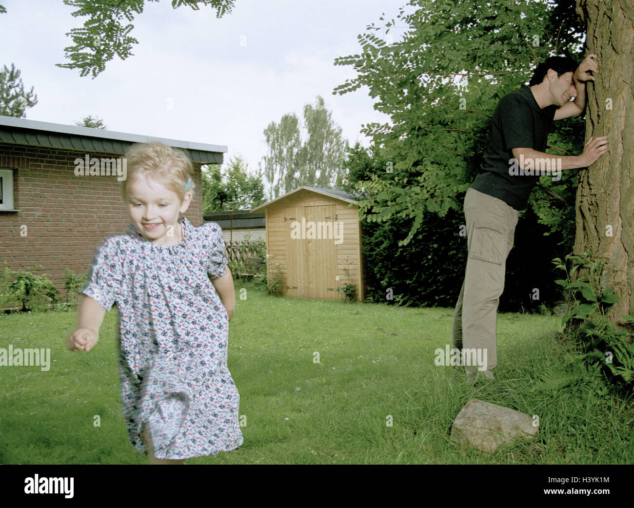 Garden, father, subsidiary, hide-and-seek, man, parent, 30-40 years, parent, single parent, single, tree, lean, - Stock Image