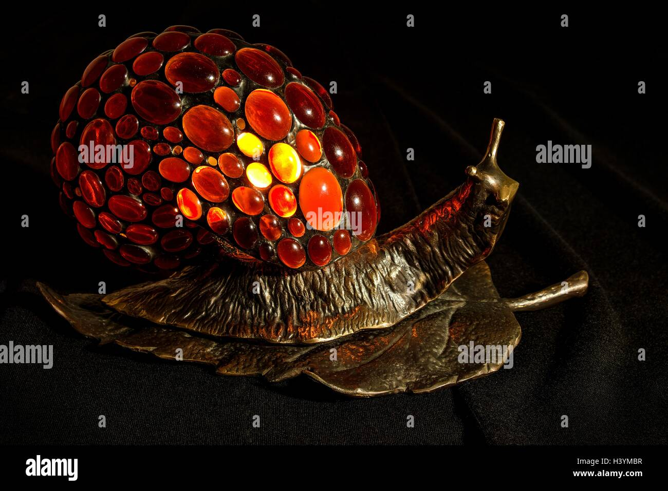 Handmade lamp in the form of a snail made of bronze and natural Baltic amber - Stock Image