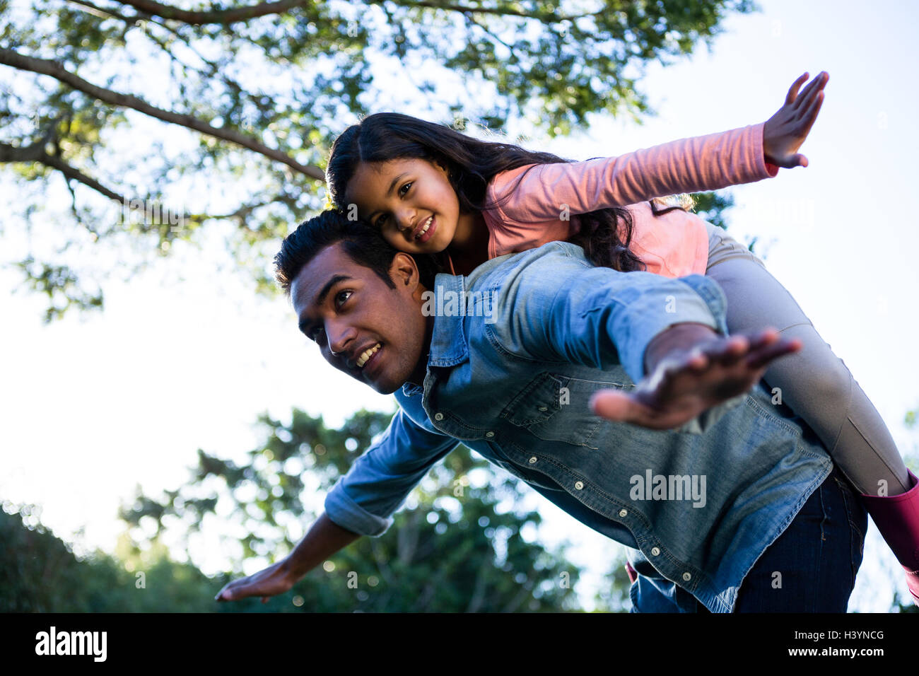 Father giving piggyback ride to his daughter - Stock Image