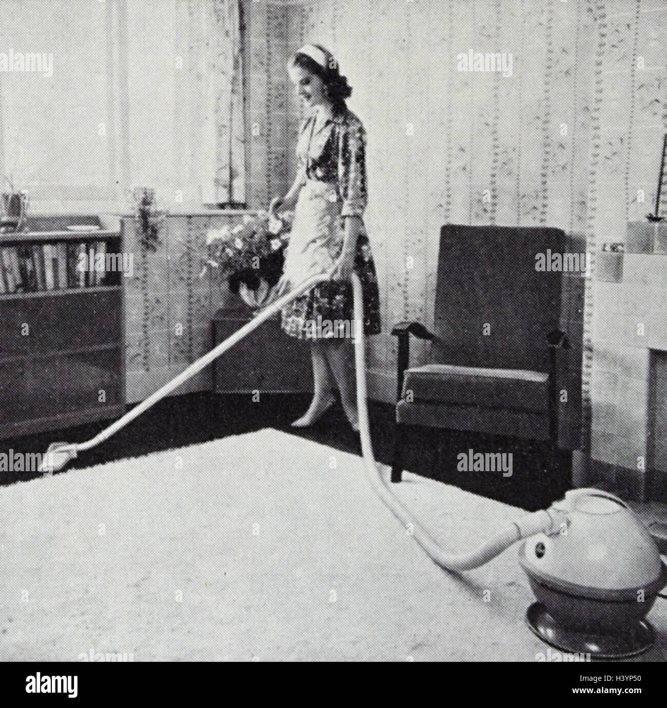 Photograph of a 1950s housewife performing some chores. Dated 20th Century - Stock Image