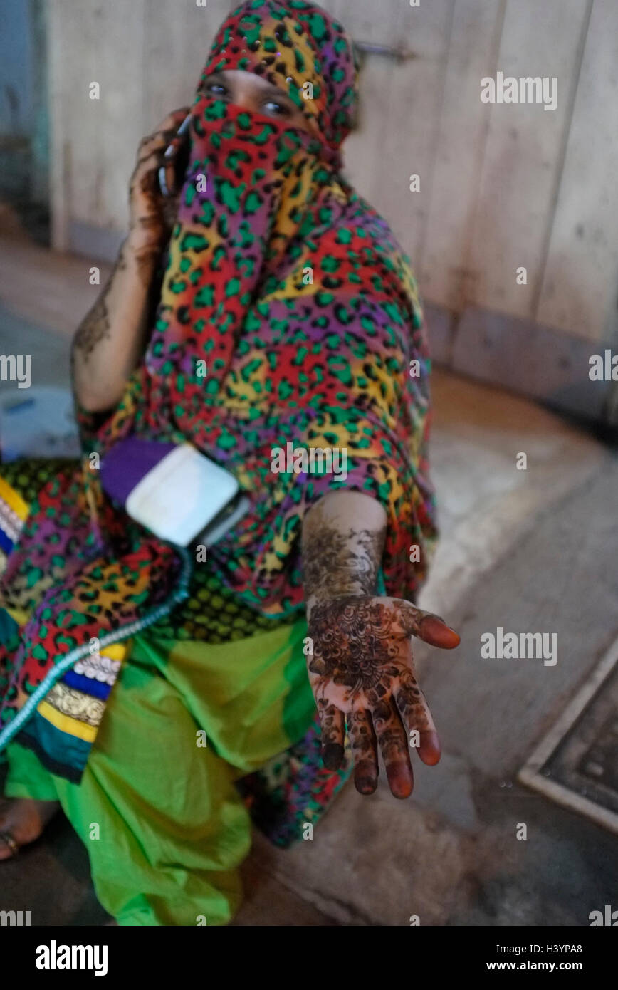 a Women in Saree and burka (burqa) speaks by mobile telephone with Mehndi  (henna) tattoos on arm and hands. Kurla, - Stock Image