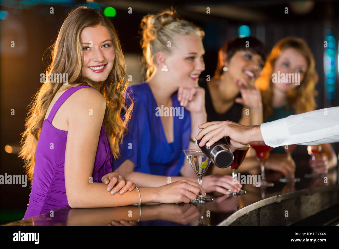 Waiter pouring cocktail in womans glass at bar counter Stock Photo