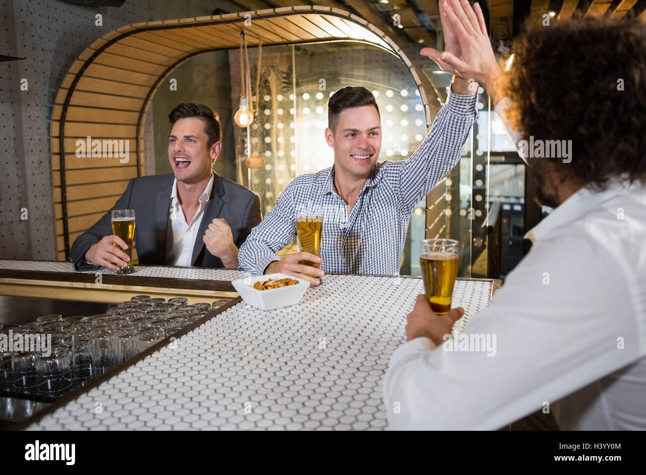 Friends giving high five while watching tv - Stock Image