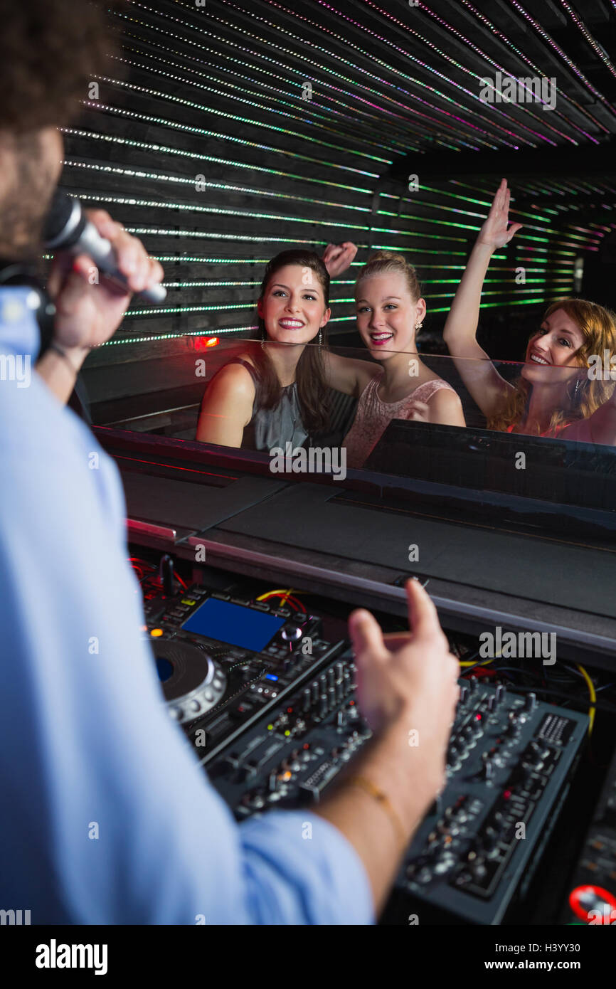 Male disc jockey playing music with three women dancing on the dance floor - Stock Image