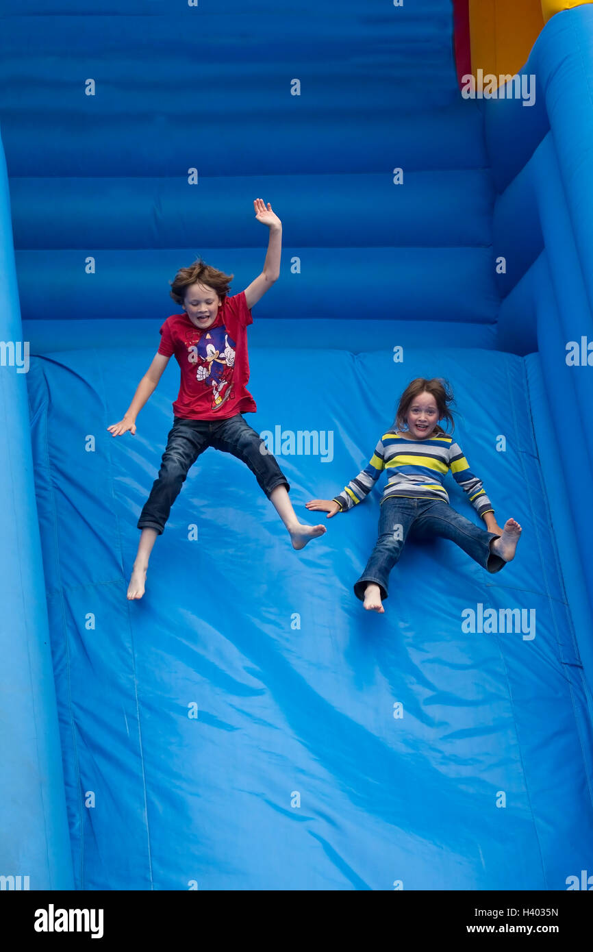 Boy and Girl hurtling down an inflatable slide in sheer delight - Stock Image