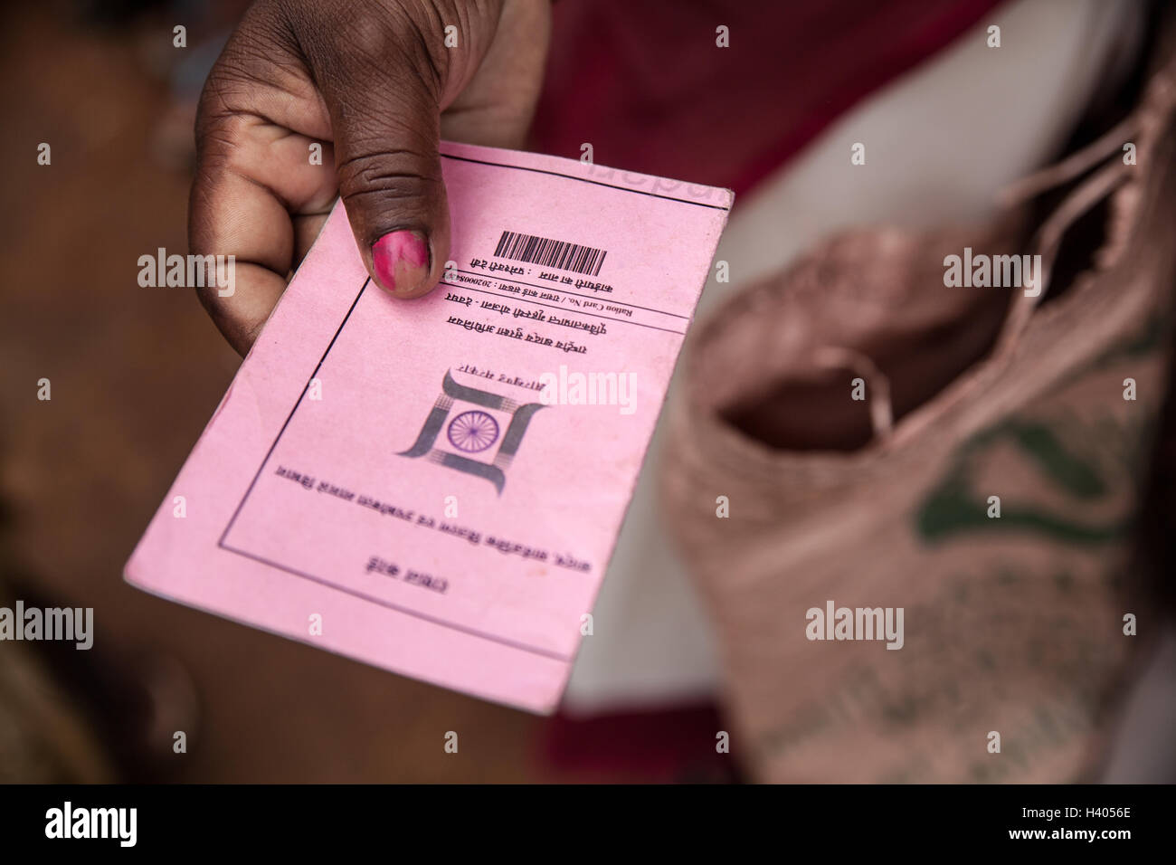 Hand of a woman showing her ration card which allows her to buy highly subsidized rice according to the National - Stock Image