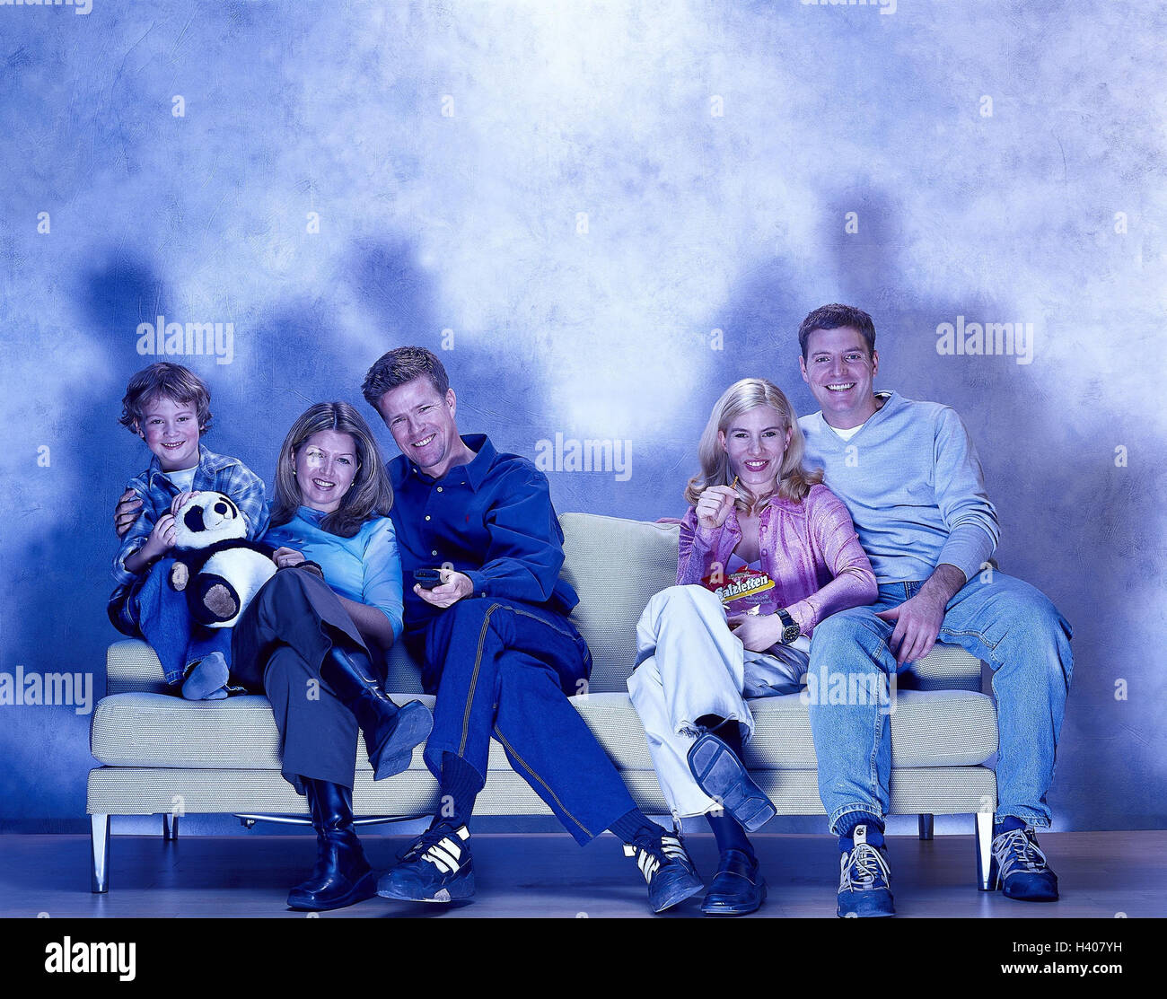 Family, couple, couch, television, remote control, saltsticks, laugh, toggle Families, couples, child, man, woman, - Stock Image