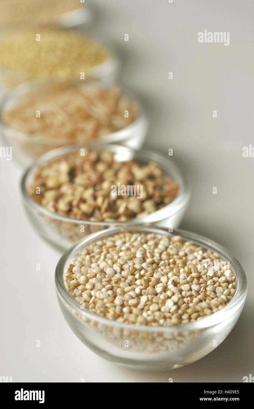 Quinoa and other gluten-free cereal grains in glass bowls, vertical image on white blurred background - Stock Image