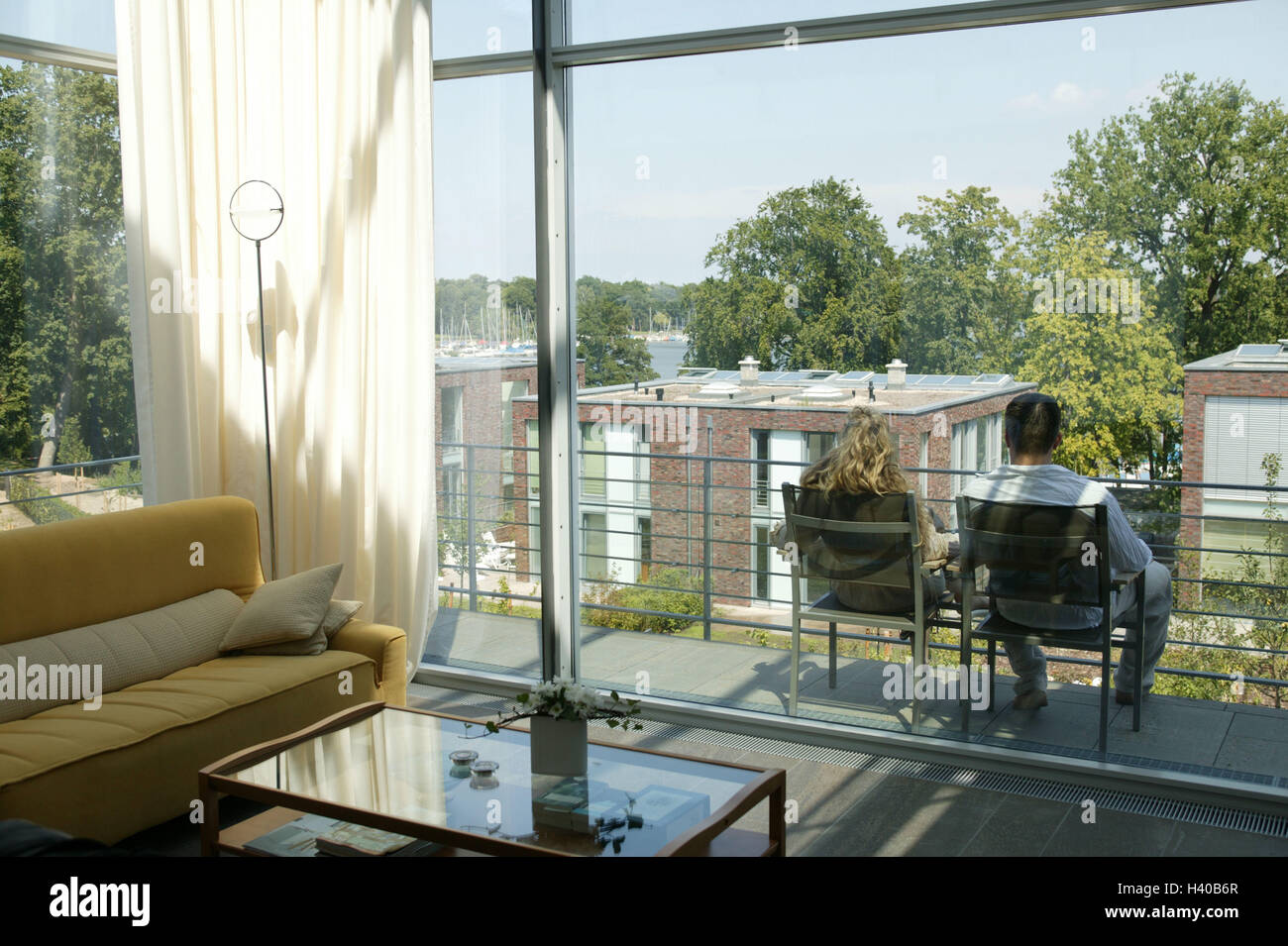 Flat, window front, couple, balcony, sit, enjoy back view, summer, residential complex, real estate, new building, - Stock Image