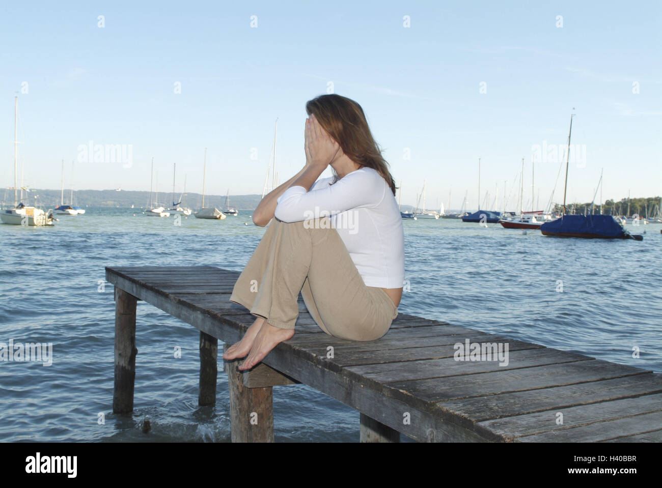 Lake, wooden jetty, woman, young, sadly, look, hands, hide, there sit, side view, bridge, 28 years, leisure time, - Stock Image