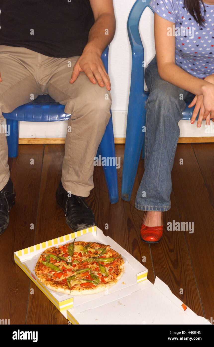 Couple, chairs, sit, resist floor, cardboard, pizza, detail, man, woman, partnership, respect, friends, self-help - Stock Image