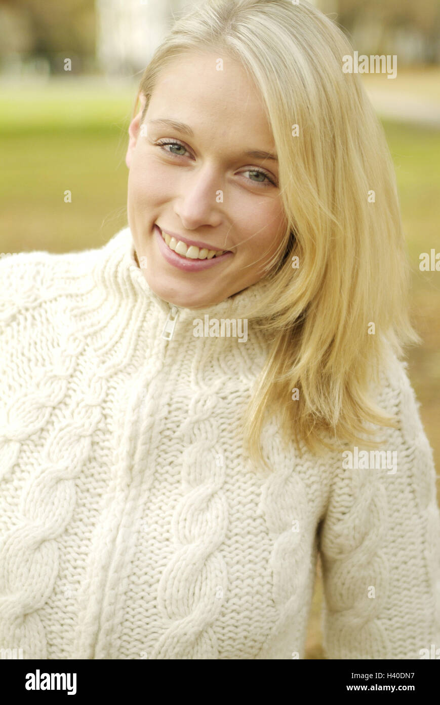 Woman, smile young, blond, portrait, leisure time, 23 years, long-haired, blue eyes, pullover, knitted pullover, - Stock Image