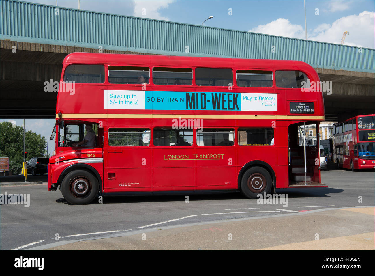 Near side view of a classic AEC Routemaster bus in London Transport livery about to pass under the Canning Town - Stock Image