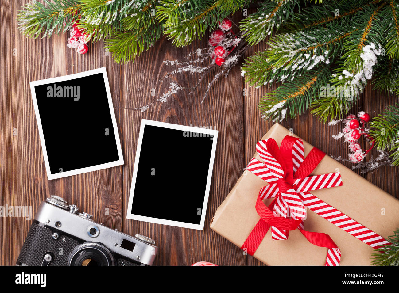 Blank Photo Frames With Christmas Gift Box, Pine Tree And Camera On Wooden  Table. Top View