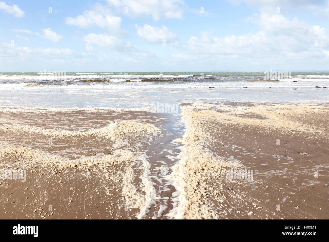 Sea foam or ocean foam on a British beach, Britain, UK - Stock Image