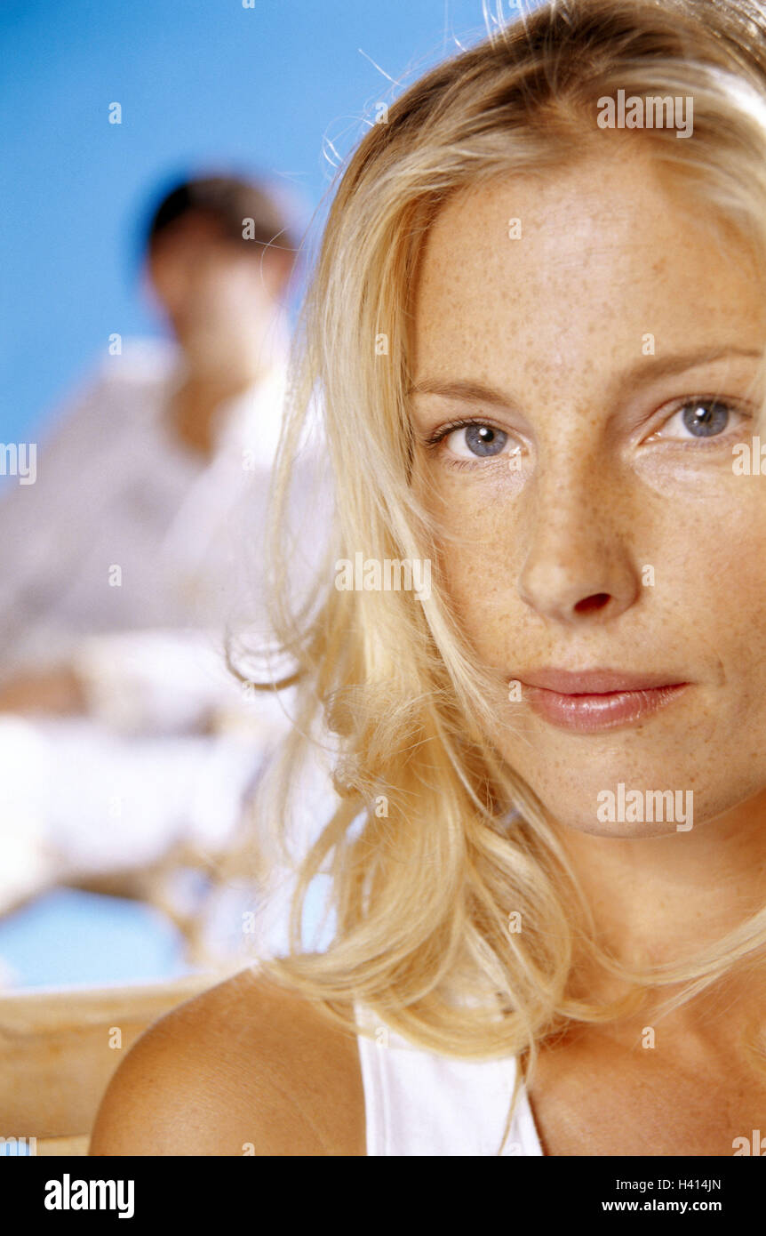 Woman, sit young, portrait, detail, background, man, blur, women's portrait, blond, long-haired, curled, seriously, - Stock Image