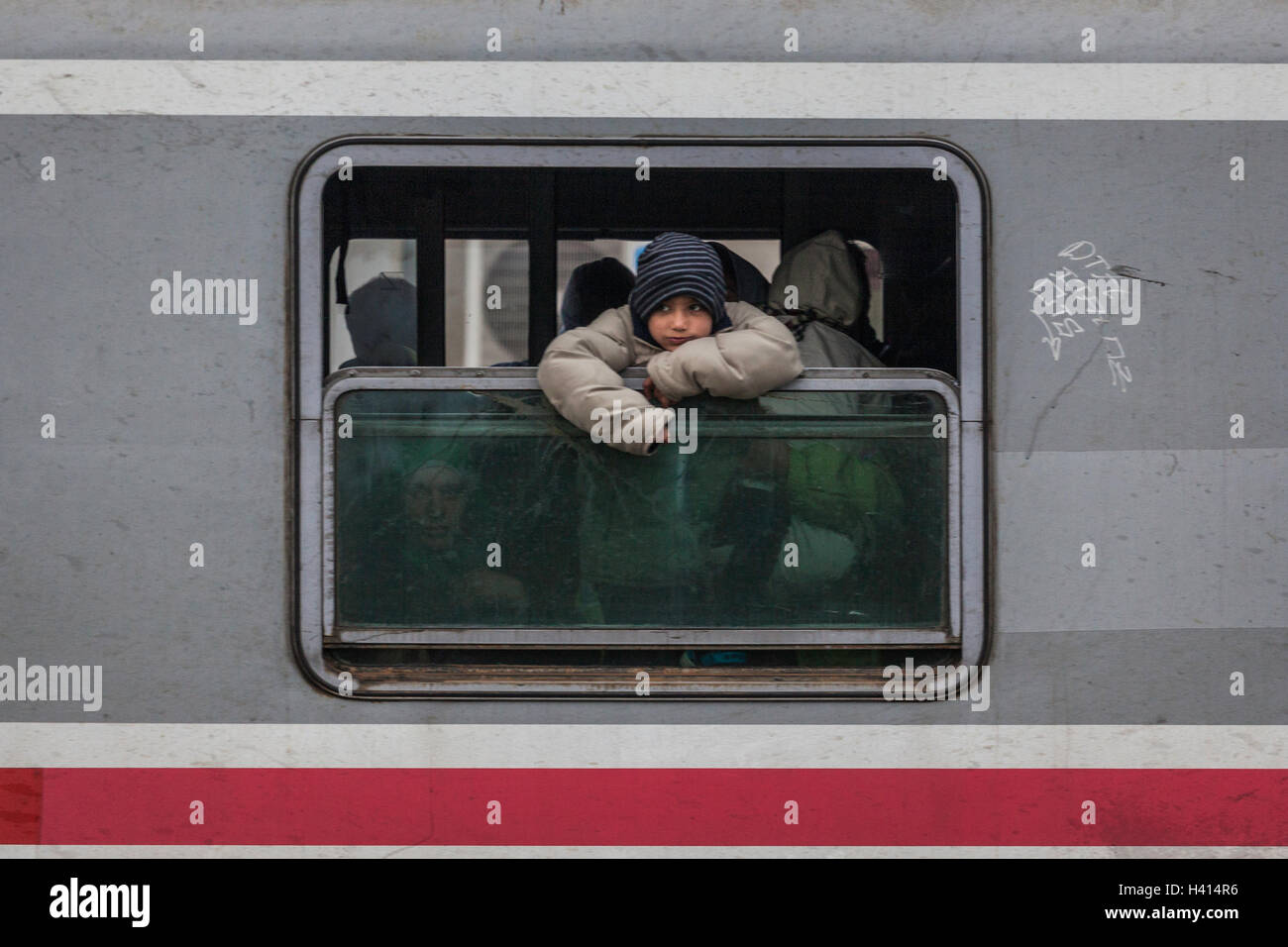 A refugee child looks through the window as they arrive from Croatia to Slovenian train station in Dobova - Stock Image