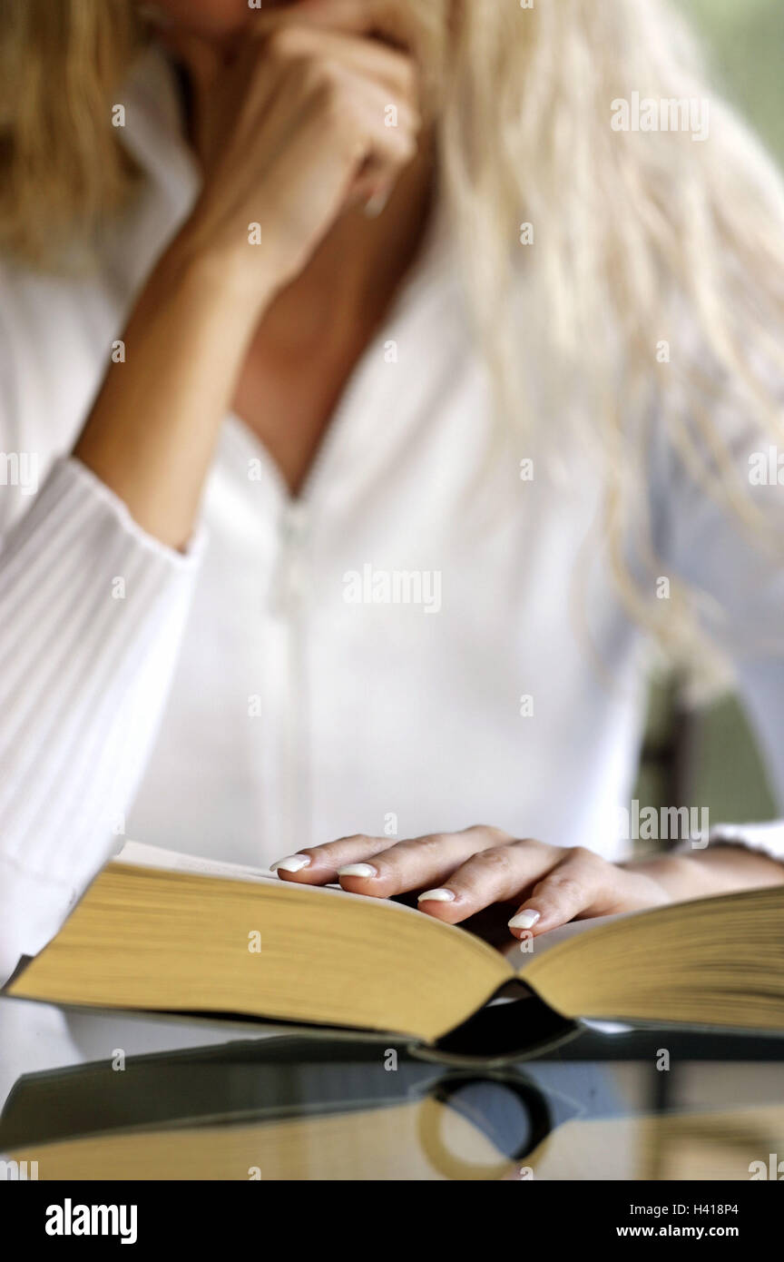 Woman, book, reading, thoughtful,  concentrate, detail   Table, sitting, rested, hands, arm, reading, literature, - Stock Image