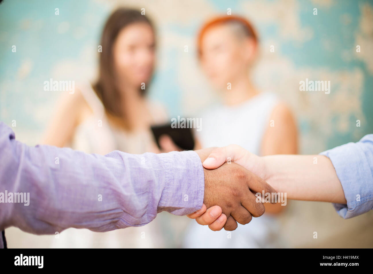 Closeup image of business partners making handshake in grunge office - Stock Image