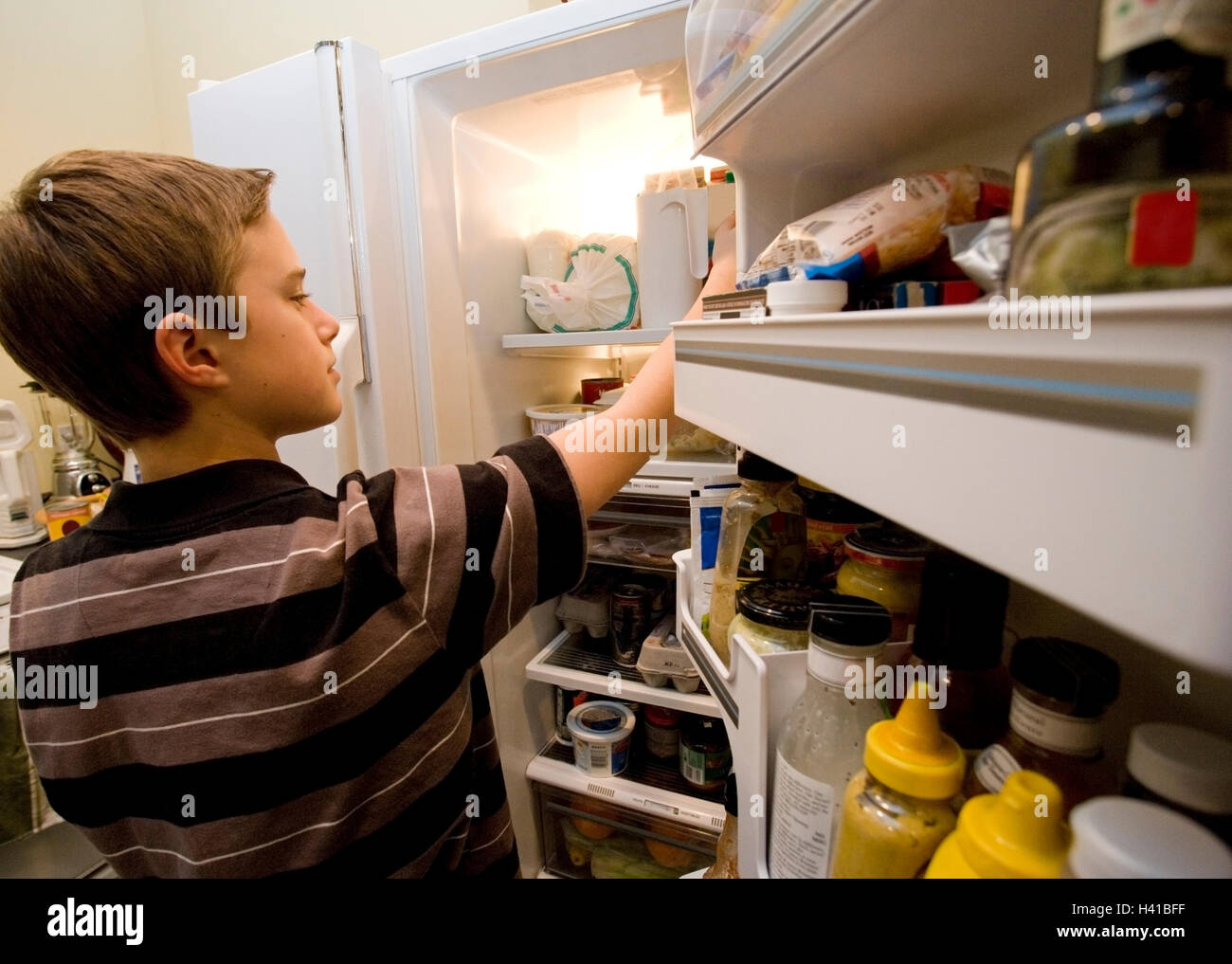 boy looking in refrigerator - Stock Image