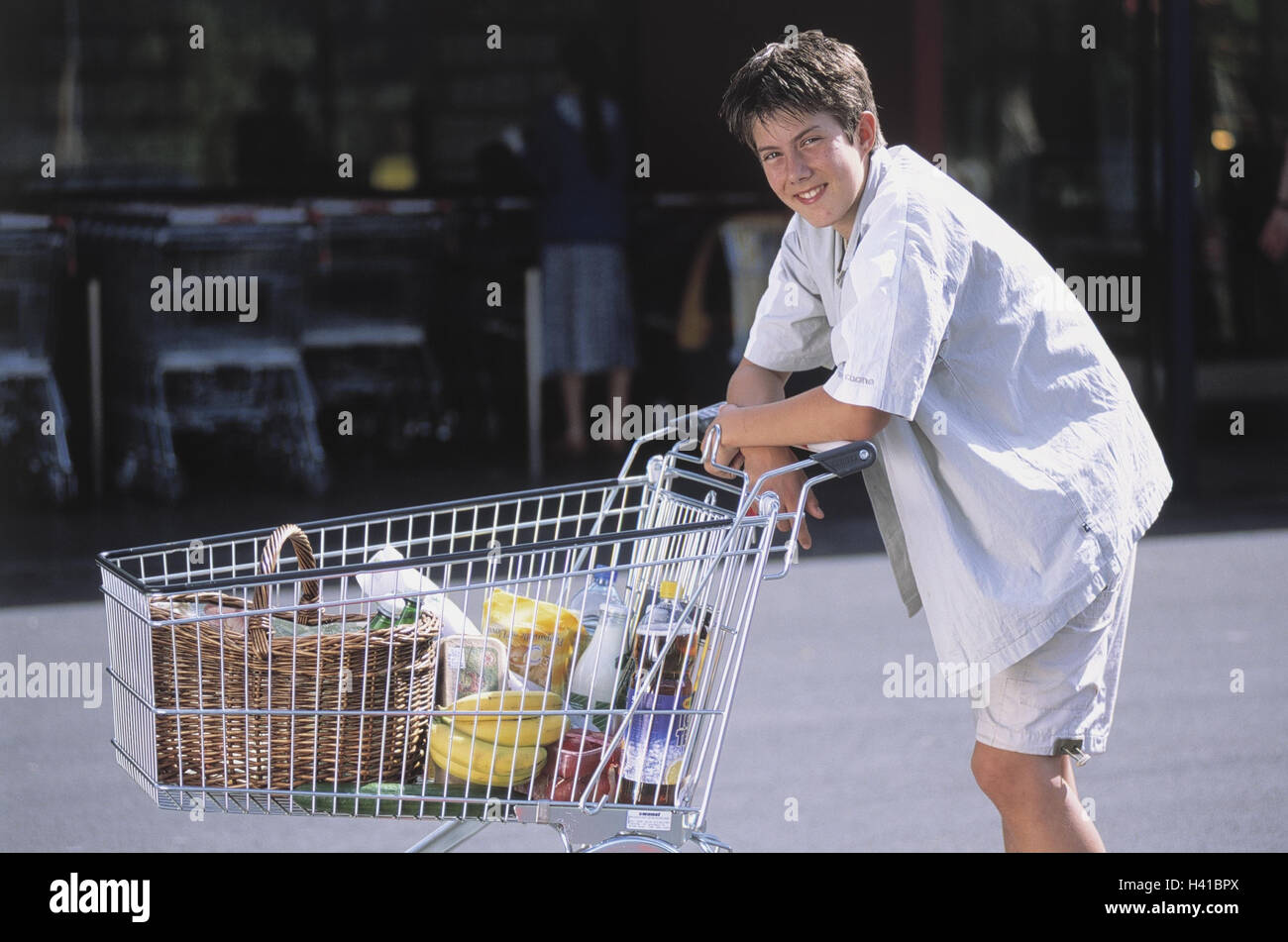 boy shopping shopping carts outside child young person teenager teenagers boy schoolboy leisure time holidays school end work job work work