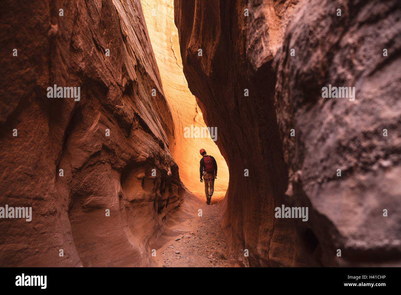 A man canyoneers through a red slot canyon in southern Utah - Stock Image