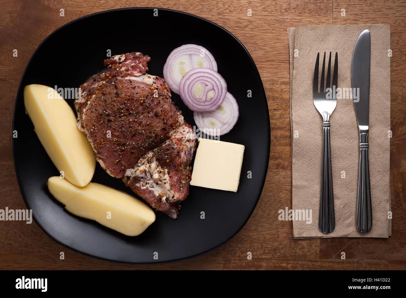 raw pork steak still life wooden background prepare food rustic cooking herbs - Stock Image