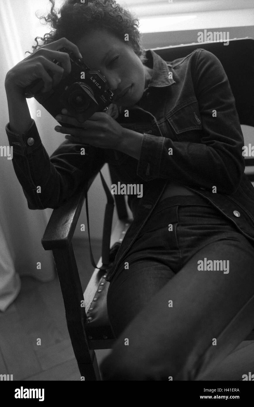 Armchairs, woman, take photos, b/w, young, dark-skinned, hair, curls, wavy, camera, photo camera, photographer, - Stock Image