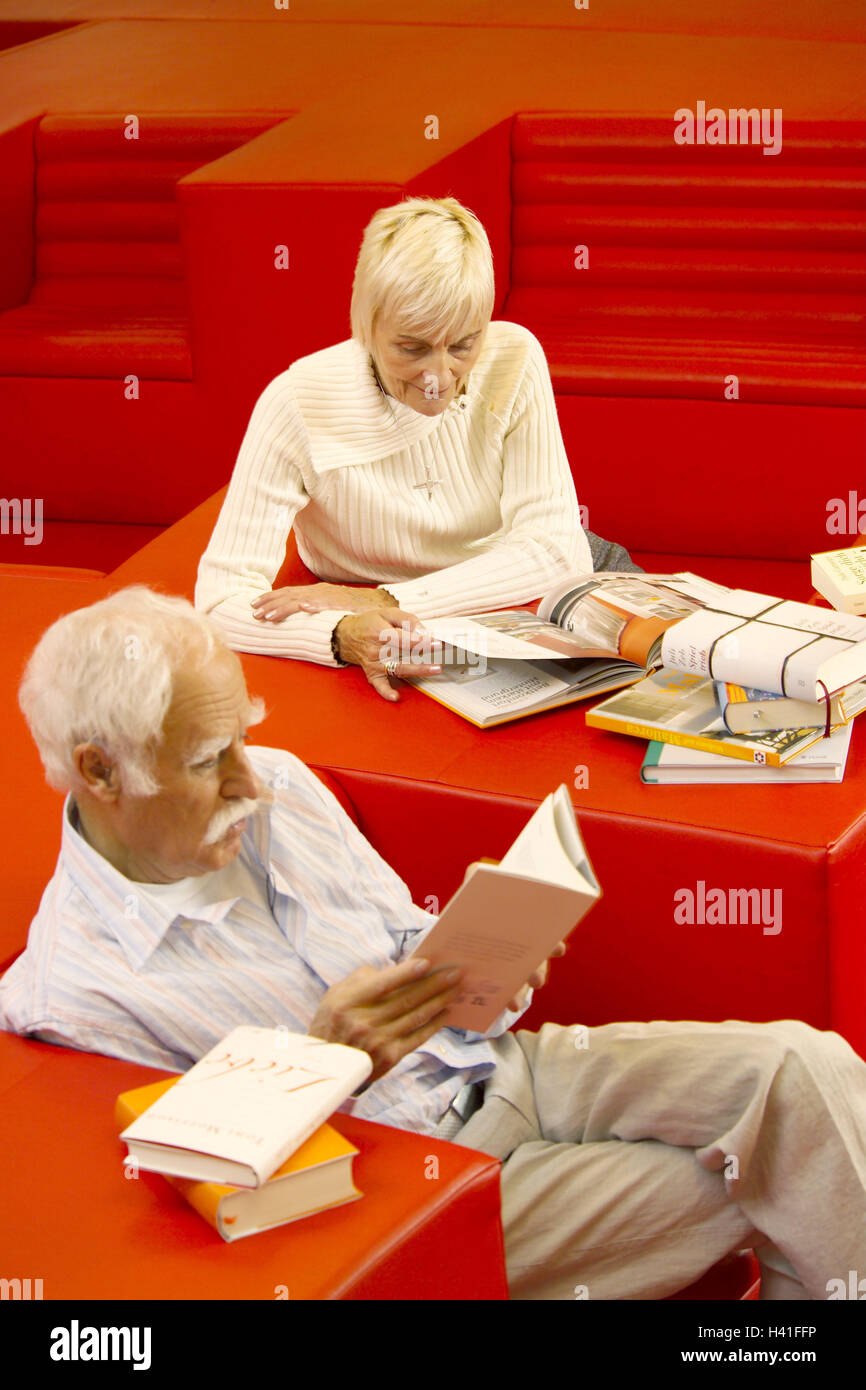 Library, Senior couple, sit, page through books, inform, browse bookstore, public library, seat opportunity, armchair, Stock Photo