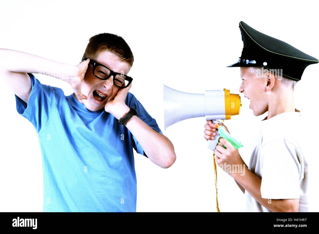Boy, police cap, megaphone, shout, friend, glasses, startled, half portrait, side view, children, brothers, friends, - Stock Image