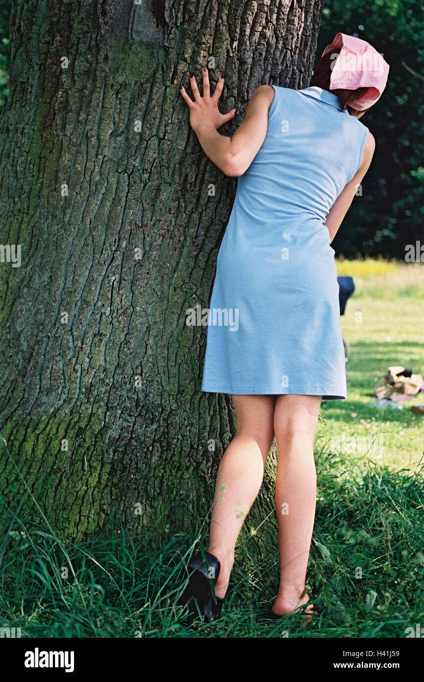 Woman, young, trunk, hide-and-seek, back view, park, game, fun, amusements, girls, young persons, teenagers, minidress, - Stock Image