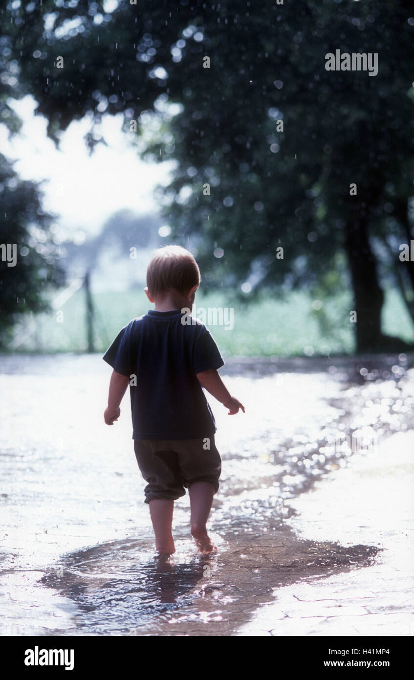 Boy, barefoot, rains, puddle, go, back view, infant, child, 3 years, leisure time, childhood, summer, summer rain, - Stock Image