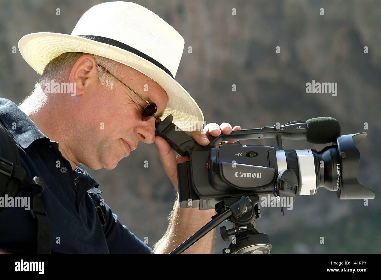 Man, side view, view, viewfinders, DP camera, tread, care, headgear, straw hat, glasses, sunglasses, hobby, leisure - Stock Image