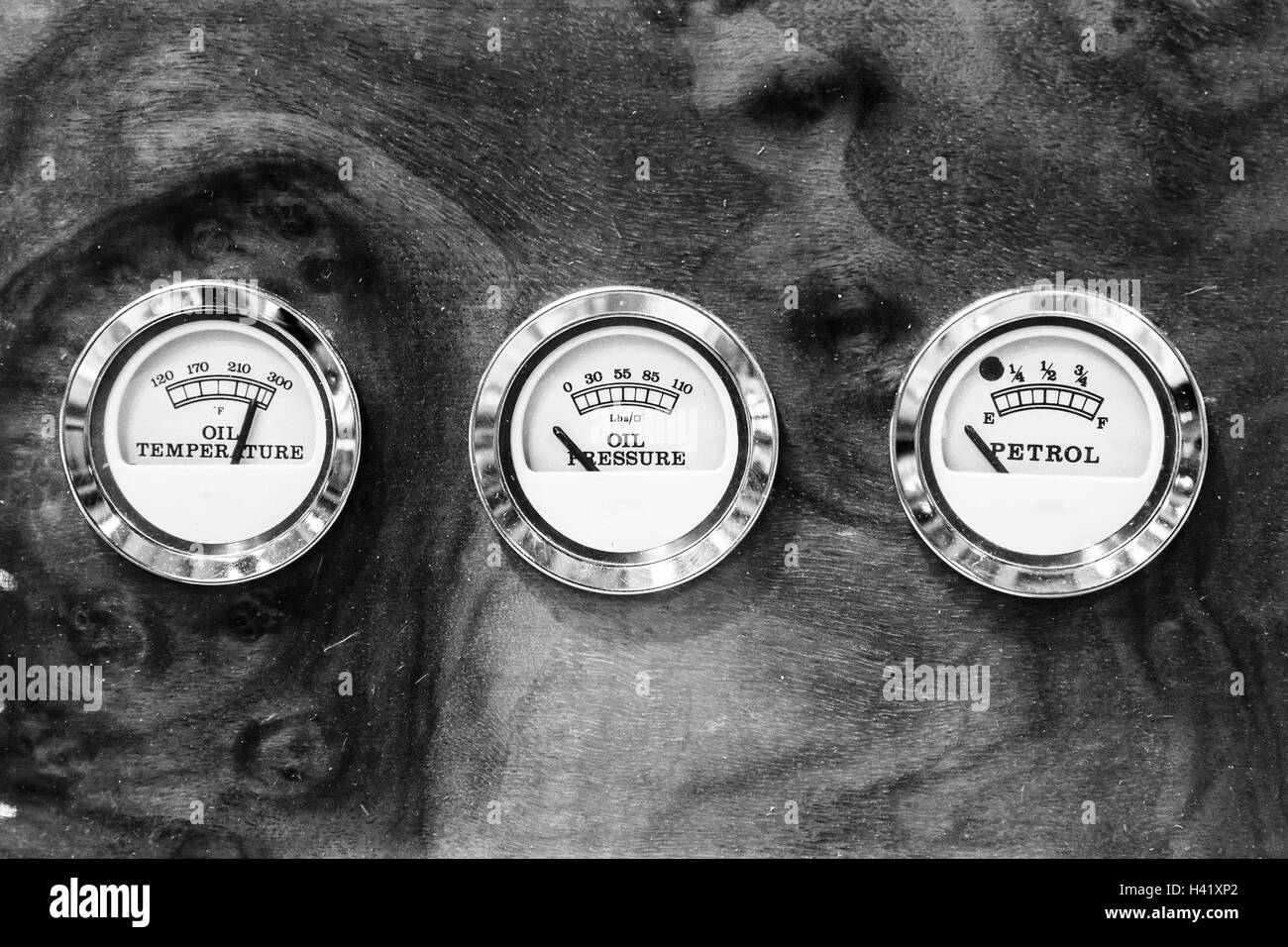 Oil temperature, oil pressure and oil level indicators on the briar dashboard of a vintage car. - Stock Image